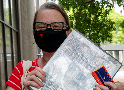 a patron wearing a face covering holding a book and her library card