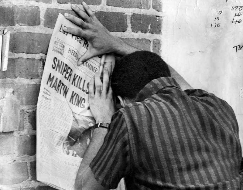 A Los Angeles resident collapses in grief while reading the details of Martin Luther King Jr.'s assassination