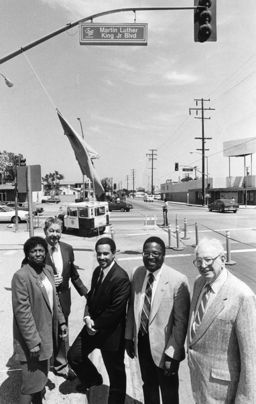 Lynwood city council members under a new MLK blvd sign