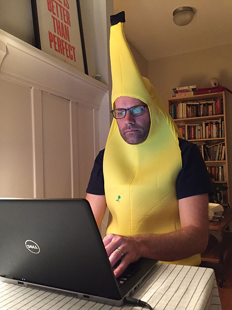 Chris Baty at a computer in a banana suit