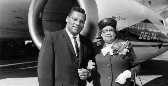 Photographer Rolland J. Curtis and his mother, Mathilda Curtis. They are standing near a Delta Airlines plane, and she is wearing a corsage.