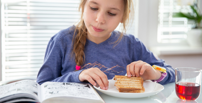 Girl reads a graphic novel while having a grilled ham and cheese sandwich