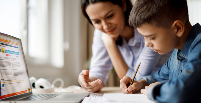 Mom helping son do his classwork using online learning.