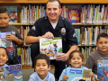 Officer Joseph Oseguera sitting down with children from the Vermont Square Branch, smiling at the camera and holding books