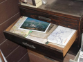 An open drawer with full of local maps