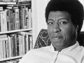 Octavia E. Butler seated by her bookcase, 1986