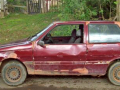 old red compact car in bad shape