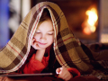 Young girl reading under a warm blanket