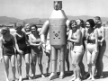 Robot on the beach surrounded by ladies in bathing suits