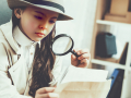 Young girl investigating photos with magnifying glass.