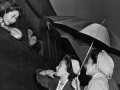 Young Japanese girls brave the early morning rain to bid farewell to friends leaving for Manzanar relocation camp