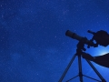 Looking up at the dark, starry night sky with a telescope