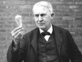 Thomas Edison holding the electric light bulb.