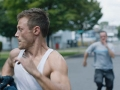 young man in tank top running away from another man