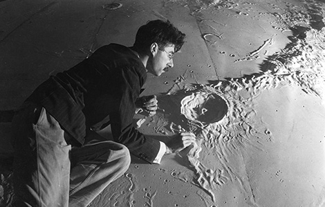 An early exhibit commissioned for the Griffith Observatory was a 38' plaster scale model section of the moon. Architect and astronomer Roger Hayward (pictured here) assured the accuracy of the model sculpted by Caspar Gruenfeld. Security Pacific National.