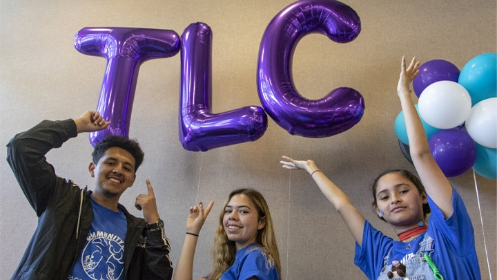 Teens pointing to purple balloons that spell TLC