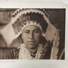 Plate 455 Tolowa Dancing Head-Dress.  Native American Tolowa man wearing a head dress, photographed looking straight into camera with plain expression