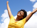 cheerful young woman with hands raised