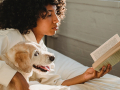 A young woman reads a book while her dog lie beside her.