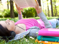 Girl reading book on sunny day in park