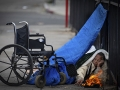Woman on the street huddled under tarp next to wheel chair with a fire burning